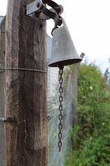 antique bell at the entrance to the ranch near the roads