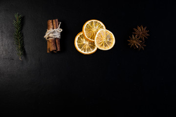 Christmas Tree Pine Branches with dry oranges. cinnamon, anise, pine on a dark background.