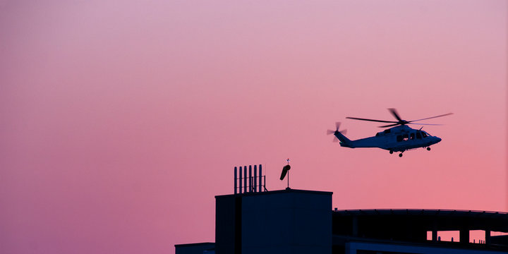 Air ambulance helicopter departing from a hospital helipad.
