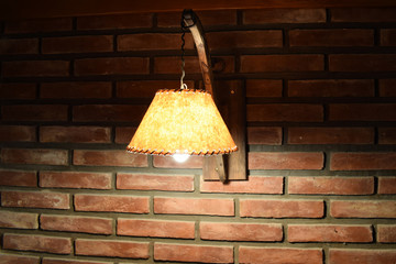 turning on an antique lamp on a red brick wall in a dark room