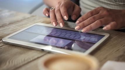 young woman works with digital tablet on a background of cup of coffee on a wooden table