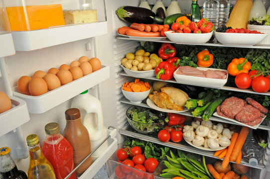 VIEW INSIDE REFRIGERATOR WITH SHELVES FILLED WITH FRESH FOOD