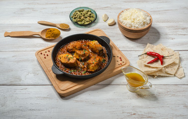 Foto op Plexiglas Klaar gerecht Bengali fish curry and set Indian spices with basmati rice on wooden table.