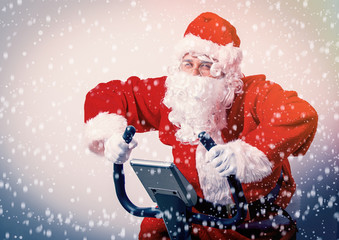 Funny Santa Claus have a fun with Exercise Bikes on white background