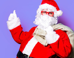 Funny Santa Claus have a fun with red eyeglasses on purple background
