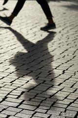 Schatten eines Fußgängers in der Innenstadt von Leipzig im Gegenlicht