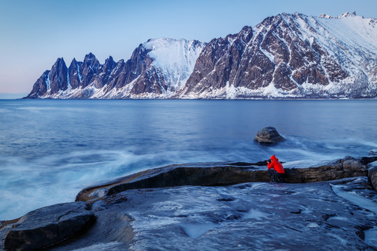 Senja island, Norway. A photographer in red jacket is taking a photo of breathtaking landscape in blue hours.