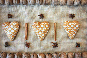 Gingerbread hearts on jute fabric surrounded by walnuts, Christmas background