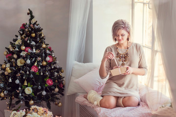 Blonde girl on the windowsill in the new year's morning and Christmas tree on background