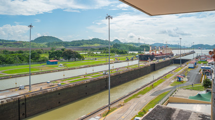 Large cargo ships pass through the Panama Canal locks.  This everyday event, provides income from both fees and tourism for the whole country.