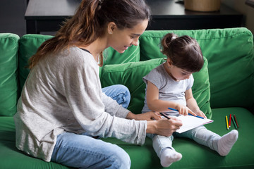 Loving young single mother coloring with little preschool cute daughter with color pencil in album sitting on green couch, sofa, babysitter playing with child, pupil, spending time together. Top view