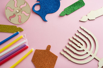 Image of Jewish holiday Hanukkah with wooden dreidel (spinning top) , menorah (traditional Candelabra) candles, children's stickers glitter craft on pink background.Top view.