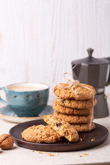 Cup of coffee, oatmeal cookies, coffee maker on white wooden background. Bright morning