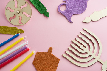 Image of jewish holiday Hanukkah with wooden dreidels (spinning top) , menorah (traditional Candelabra) candles, children's stickers glitter craft on pink background.Top view.