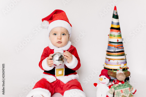 2521b231ad6b Little girl wearing santa claus red dress sitting on the floor holding  small Christmas ball and smiles over white background,Christmas concept.
