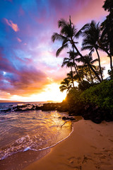 Footprints in the Sand with Awesome Colorful Sky at Sunset and Calm Ocean Water Coming on Sandy Beach Shore with Palm Trees Silhouette and Lush Greenery at Secret Beach in Maui Hawaii