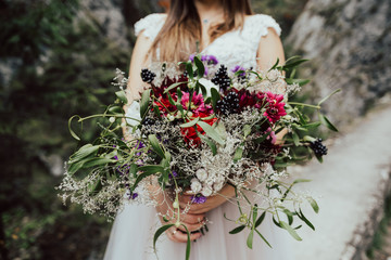 Wedding bouquet with autumn flowers in hands of the bride.Bride holding colorful wedding bouquet against dress.The bride with a bouquet on beautiful rocks background.Rustic Wedding.