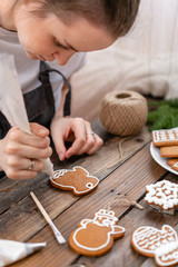 cookies in the form of mittens. A young girl decorates ginger cookies Christmas winter morning. Woman draws Icing on honey gingerbread . Wooden brown table. copy space.