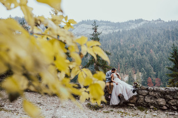 Beautiful wedding couple kissing in the mountains.Romantic groom and bride in gorgeous wedding dress sits on the rocks in the green mountains.Scenic landscape view.