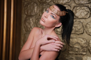 Pretty Tan Brunette Posing. Egypt Style Rich Luxury Woman With Jewellery on Golden Background.