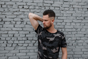 Handsome attractive young man in a stylish camouflage military gray T-shirt with a stylish hairstyle and beard, posing near a gray brick wall. Fashionable urban guy.