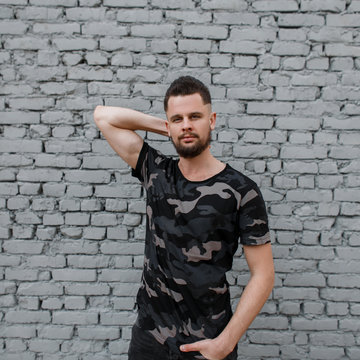 Handsome attractive young man in a stylish camouflage military gray T-shirt with a stylish hairstyle and brutal beard, posing near a gray brick wall. Fashionable modern guy.