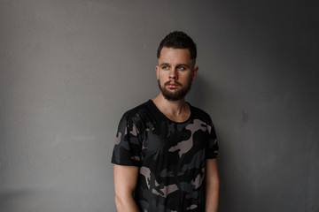 Attractive young man with a stylish hairstyle and brutal beard in a modern military camouflage T-shirt stands near a gray wall. Fashionable modern guy
