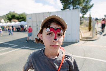 Portrait of girl with face paint standing on road during sunny day