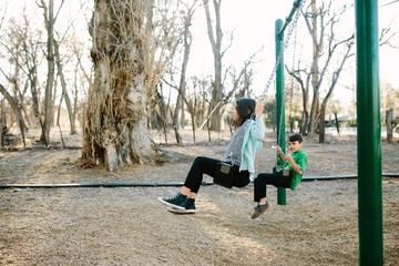 Side view of siblings swinging against bare trees in playground