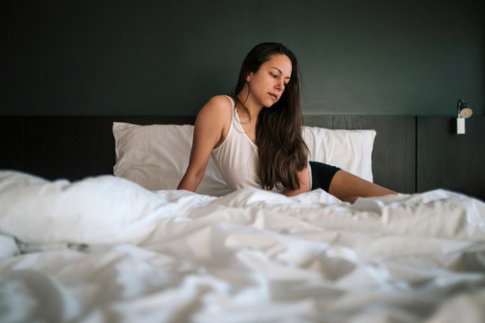 Thoughtful woman looking away while relaxing on bed at home