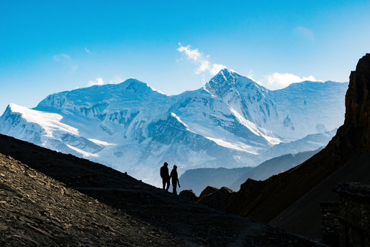 Silhouette couple holding hands while hiking on mountain against blue sky