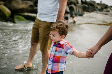 Cropped image of parents holding son's hands while walking at beach