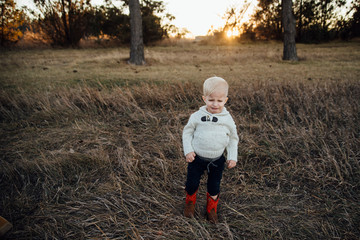 Full length of cute boy crying while standing on field during sunset