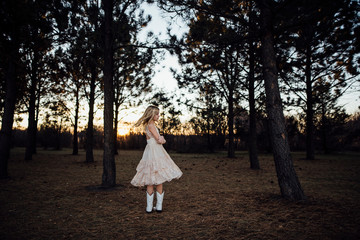 Full length of girl wearing white dress standing in forest during sunset