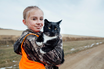 Side view portrait of smiling girl carrying black cat while standing on dirt road against sky