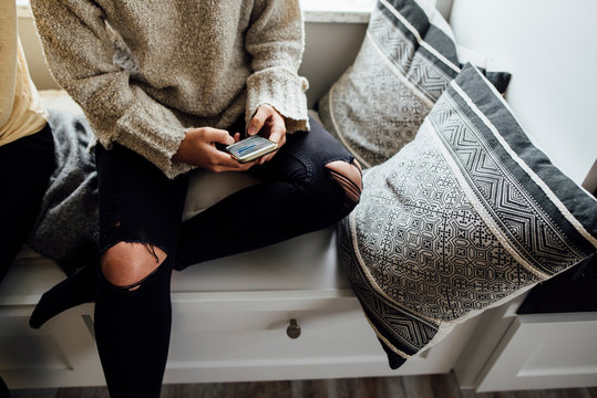 Midsection of woman using mobile phone while sitting on alcove window seat at home