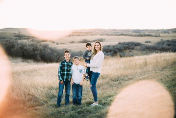 Portrait of mother with sons standing on field during sunset