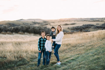 Full length portrait of mother with sons standing on field during sunset