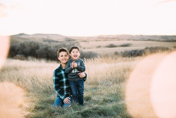 Portrait of smiling boy with cheerful brother on field during sunset