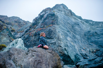 Low angle view of girl sitting on rock against mountains