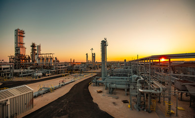 Petrochemical plant at Permian Basin against clear sky during sunset