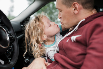 Daughter kissing father while sitting in car