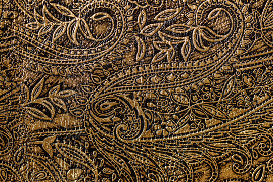 Texture of golden brown genuine leather close-up, with embossed floral trend pattern, wallpaper or banner design