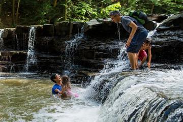 Family enjoying in waterfall in forest