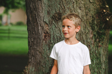 Thoughtful cute boy looking away while standing against tree in park