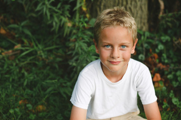 High angle portrait of smiling cute boy sitting on field in park