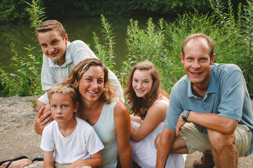 High angle portrait of smiling family sitting by river in park
