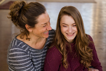 High angle view of happy mother and daughter sitting on floor at home
