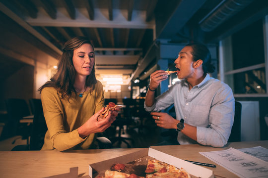 Business man and woman eating pizza late in the night at office