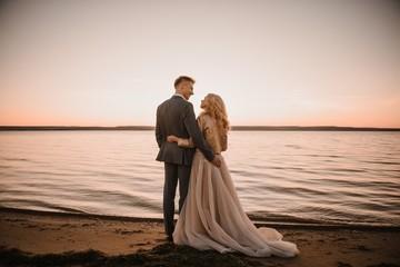 Stylish wedding photo shoot in nature at sunset.